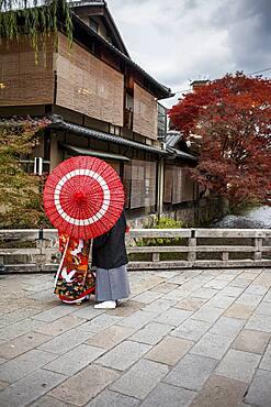 Couple dressed in traditional costume, in Shirakawa-minami-dori, Gion district, Kyoto. Kansai, Japan.