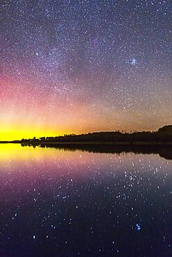 The rising autumn stars and constellations over and reflected in the lake at Police Outpost Provincial Park, in southern Alberta, on September 26, 2016. The stars of Auriga and Taurus are rising, including the Pleiades at upper right. Capella is the bright star above right centre; Aldebaran is below right in the sky. Both are reflected in the still water, along with the Hyades and Pleiades star clusters. A mild aurora is at left.