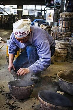 Takahiro Koizumi is preparing spoon to load molten iron, that will put in a molds to make a iron teapot or tetsubin, nanbu tekki, Workshop of Koizumi family, Morioka, Iwate Prefecture, Japan