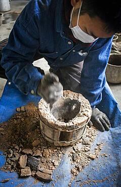 Kohei ishimori is clearing a outer mold for make a new design of a iron teapot or tetsubin, nanbu tekki,Workshop of Koizumi family,craftsmen since 1659, Morioka, Iwate Prefecture, Japan