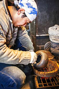 Takahiro Koizumi is putting the finishing touches at iron teapot or tetsubin, nanbu tekki, Workshop of Koizumi family,craftsmen since 1659, Morioka, Iwate Prefecture, Japan