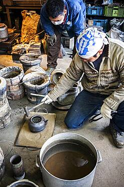 This is an important moment in the construction process. They are checking that no water escapes from the new iron teapot or tetsubin, nanbu tekki,Workshop of Koizumi family,craftsmen since 1659, Morioka, Iwate Prefecture, Japan