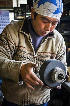 Takahiro Koizumi is preparing the inner mold, to make a iron teapot or tetsubin, nanbu tekki,Workshop of Koizumi family,craftsmen since 1659, Morioka, Iwate Prefecture, Japan