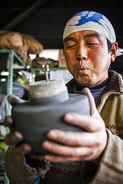 Takahiro Koizumi is preparing the inner mold, to make a iron teapot or tetsubin, nanbu tekki, Workshop of Koizumi family,craftsmen since 1659, Morioka, Iwate Prefecture, Japan