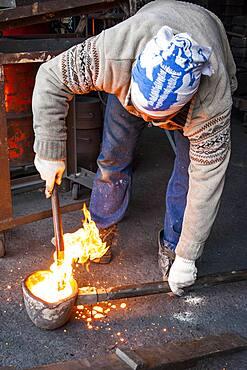 Waiting for the right temperature. Takahiro Koizumi carries molten iron with spoon to pour it into the mold, to make a iron teapot or tetsubin, nanbu tekki,Workshop of Koizumi family,craftsmen since 1659, Morioka, Iwate Prefecture, Japan