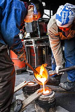 Takahiro Koizumi and his assistant Kohei ishimori are pouring molten iron into the mold, to make a iron teapot or tetsubin, nanbu tekki,Workshop of Koizumi family,craftsmen since 1659, Morioka, Iwate Prefecture, Japan