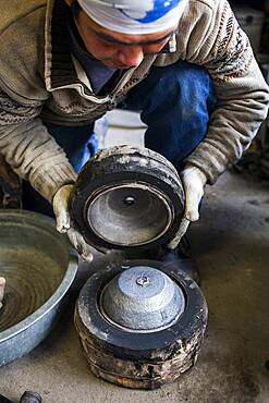 Takahiro Koizumi is opening the mold Just  after solidifying the molten iron. He casts the first look at new iron teapot or tetsubin, nanbu tekki, Workshop of Koizumi family,craftsmen since 1659, Morioka, Iwate Prefecture, Japan
