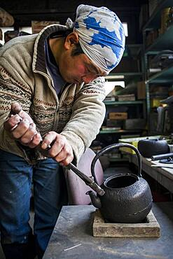 Takahiro Koizumiis putting the handle at iron teapot or tetsubin, nanbu tekki, Workshop of Koizumi family,craftsmen since 1659, Morioka, Iwate Prefecture, Japan