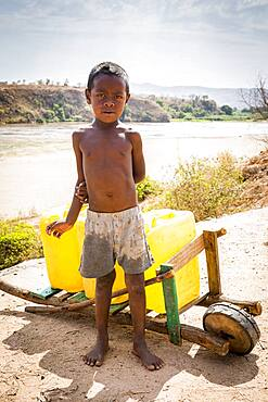 Child working in the distribution of water in Containers, Morondava, Madagascar