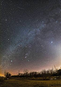 A horizon-to-zenith panorama of the winter consellations on a March evening as they set into the southwest. Orion is at bottom centre, with his Belt pointing down to Canis Major and up to Taurus. Gemini and Auriga are at top, in this case near the zenith overhead. The bright star clusters, M44, the Beehive, (at left) and M45, the Pleiades, (at right) flank the Milky Way. M45 is embedded in the Zodiacal Light. The star clusters M35 in Gemini and M41 in Canis Major are also visible as diffuse spots, as are several other star clusters. A couple of satellite trails are visible.