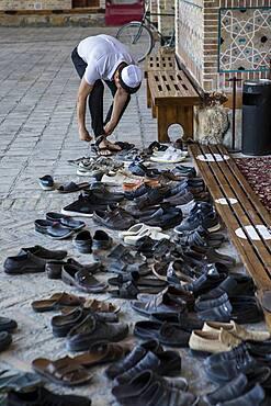 Believer takes off his shoes, in Bolo Hauz Mosque, Bukhara, Uzbekistan