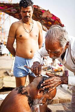 Baeber shaving the head and beard of a pilgrim, Dashashwamedh ghat (main ghat), in Ganges river, Varanasi, Uttar Pradesh, India.