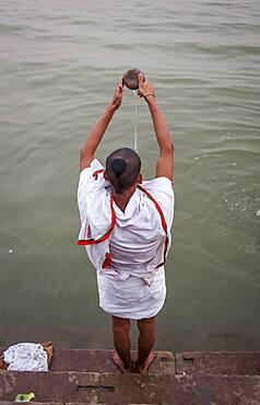 A man praying, in the ghats of Ganges river, Varanasi, Uttar Pradesh, India.