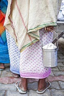 Widows begging, widow holds the container that widows usually carry to keep the food that they obtain begging, Vrindavan, Mathura district, India