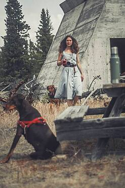 An attractive brunette woman brings two cups of coffee to a table while two dogs are around her. Yukon Territory, Canada