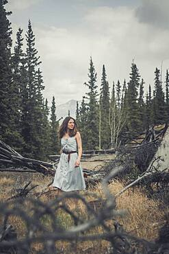 An attractive young woman walks in her jeansdress over an abandoned grazing ground in the bush. Yukon Territory, Canada