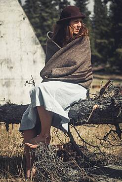 An attractive young woman sits on a log wrapped in a woollen blanket. Yukon Territory, Canada