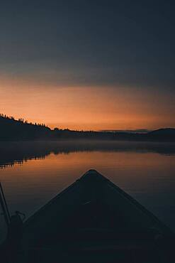 Long before the sun rises the horizon glows orange and a canoe floats over the quiet water. Yukon Territory, Canada.
