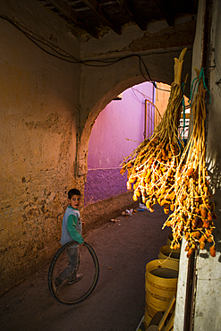 Boy plays with a wheel in Midelt's bazaar