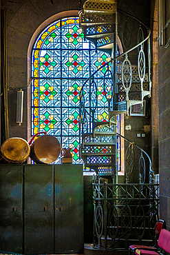 A spiraling metal staircase in front of a stained glass window, Addis Ababa, Ethiopia