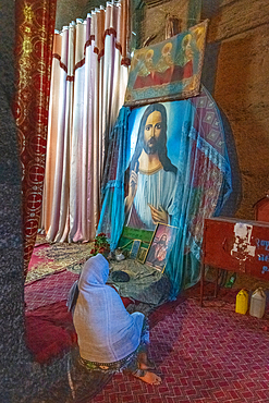 A woman sits in front of a painting of jesus Christ inside the church of Bet Medhane Alem (Church of the World Savior) in Lalibela, Ethiopia