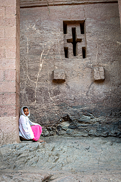 A young girl sitting against the walls of Bet Medhane Alem (Church of the World Savior) in Lalibela, Ethiopia