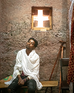 A man rests on a bench inside the rock hewn monolithic church of Bet Maryam (Church of St. Mary) in Lalibela, Ethiopia