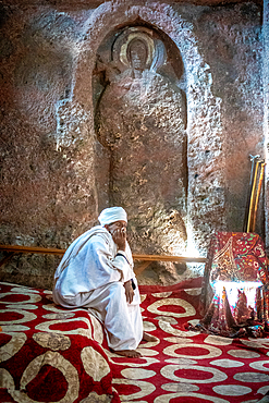 A man sits in front of a worn sculpture inside Bet Golgotha (House of Golgotha Mikael), known for its arts and said to contain the tomb of King Lalibela) in Lalibela, Ethiopia