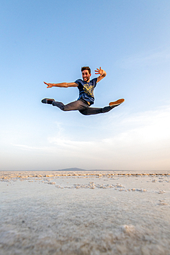 A man leaps and dances in the middle of salt flats Danakil Depression, Ethiopia