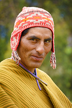 Quechua man of Misminay village wearing traditional woven poncho and knitted ch'ullu hat; Sacred Valley, Peru.