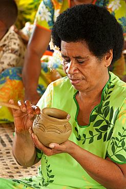 Woman making traditional pottery in Lawai village, Viti Levu Island, Fiji.