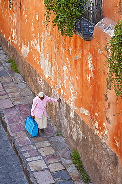 Elderly woman walking along street with her hand on a wall to steady herself; San Miguel de Allende, Guanajuato, Mexico.
