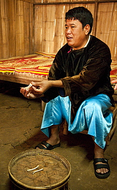 Local shaman explaining how he interprets chicken bones that people bring to him for guidance, in the Lisu village of Sridongyen in rural Chiang Mai Province, Thailand.