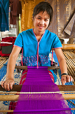 Young woman weaving cloth on loom; Patara Elephant Farm, Chiang Mai Province, Thailand.