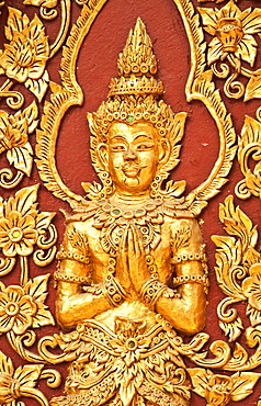 Golden Buddha figure detail on wall of Wat Mahawan Buddhist temple in Chiang Mai, Thailand.