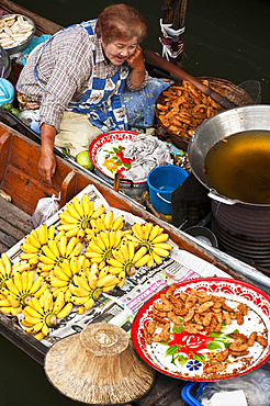 Woman selling food from boat at Damnoen Saduak Floating Market in Ratchaburi, Thailand.