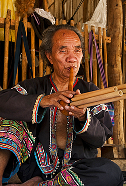 Man playing a type of flute at Baan Tong Luang, village of Hmong people in rural Chiang Mai province, Thailand.