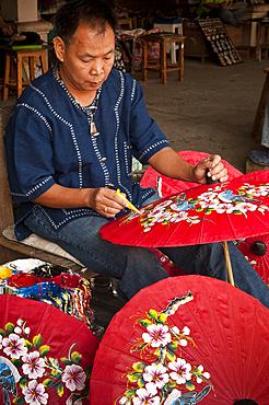 Man painting umbrellas at The Umbrella Factory in Chiang Mai, Thailand.