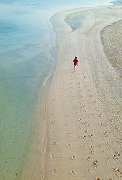 Man walking on beach next to Burj Al Arab Hotel, Dubai, United Arab Emirates.