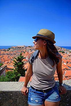 Young adult woman looking at Old Town of Dubrovnik from city walls, Croatia