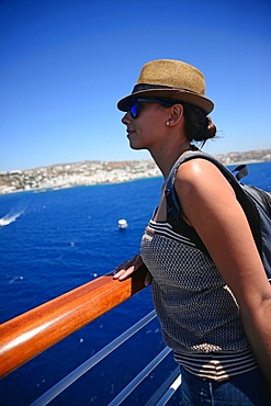 Young woman looking at Mykonos from cruise deck