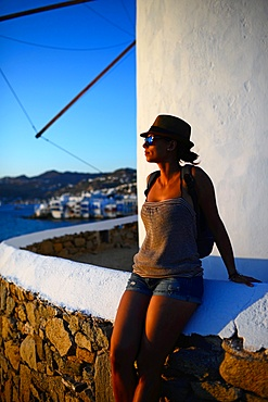 Young woman enjoying sunset from traditional windmills (Kato Milli) in Mykonos town, Greece