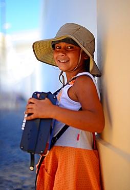 Girl playing the accordion in the streets of Santorini, Greek Islands, Greece