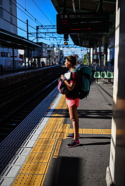 Young female backpacker in train station, Japan