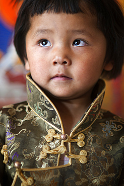 Portrait of Young Tibetan boy in traditional costume next to Potala palace Lhasa Tibet China