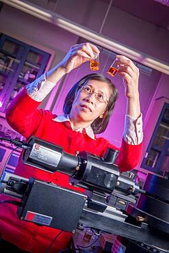Scientist in Lab, holding up vials of liquid