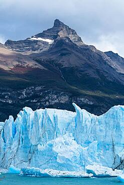 The jagged face of Perito Moreno Glacier and Lago Argentino in Los Glaciares National Park near El Calafate, Argentina.  A UNESCO World Heritage Site in the Patagonia region of South America.  Icebergs from calving ice from the glacier float in the lake.  Behind is the peak of Cerro Moreno with waterfalls on its face.