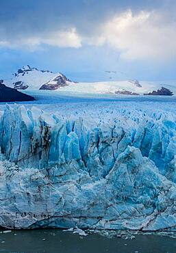 The jagged face of Perito Moreno Glacier and Lago Argentino in Los Glaciares National Park near El Calafate, Argentina.  A UNESCO World Heritage Site in the Patagonia region of South America.  Icebergs from calving ice from the glacier float in the lake.  In the distance is Cerro Gardener.