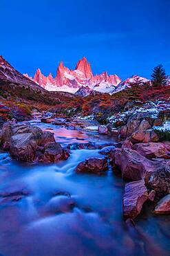 The Fitz Roy Massif in pastel pre-dawn morning twilight.   Los Glaciares National Park near El Chalten, Argentina.  A UNESCO World Heritage Site in the Patagonia region of South America.  Mount Fitz Roy is in the tallest peak in the center.  The creek in the foreground is the Arroyo del Salto.