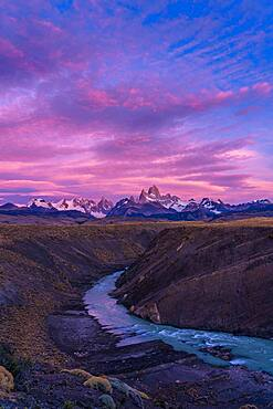 Colorful clouds in the predawn sky over Mount Fitz Roy and the Rio del las Vueltas.  Los Glaciares National Park near El Chalten, Argentina.  A UNESCO World Heritage Site in the Patagonia region of South America.